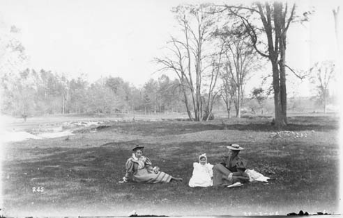 Two women and a child seated in Black Creek, Weston