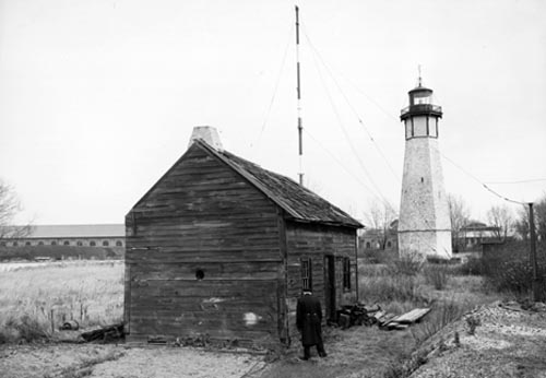 Mr. Raden Muller, lighthouse keeper for the Gibralter Point Lighthouse, shown near to his cottage, just prior to its demolition