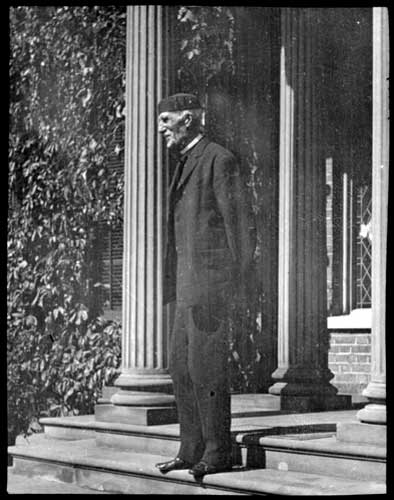 Goldwyn Smith, standing in front of his home, the Grange, on Dundas Street West, Toronto